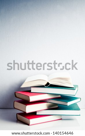 Blank open book on a green and red stack of books in balance - stock photo