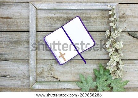 Blank open book with purple ribbon and wood cross in rustic wooden frame with flower border - stock photo
