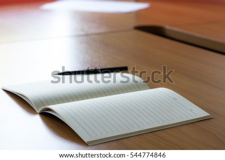 Blank open memory book with pen on the wooden table.