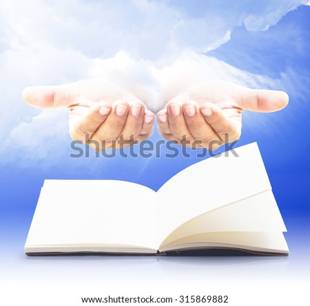 Blank opened book, diary, photo album over human open empty hand with palms up over amazing blue sky background. Book of life concept. - stock photo