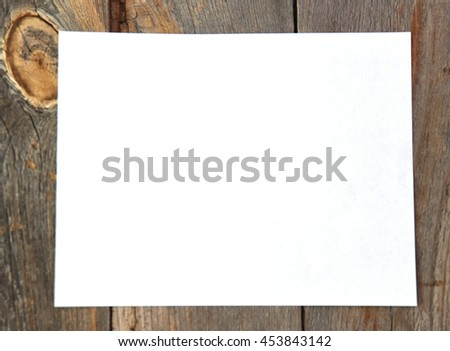 Blank or empty piece of paper on a rustic wood table for a vintage concept - stock photo