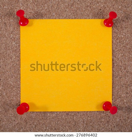 Blank orange note paper pinned to a Noticeboard. - stock photo