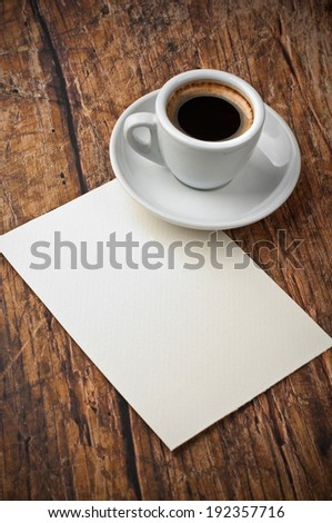 Blank paper and coffee cup on wood table - stock photo