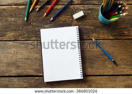 Blank paper and colorful pencils on old wooden table - stock photo
