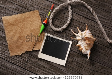 Blank paper and instant photo with fishing bait,shell and string on wooden background
