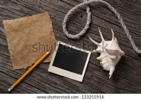 Blank paper and instant photo with pencil, shell, and string on wooden background
