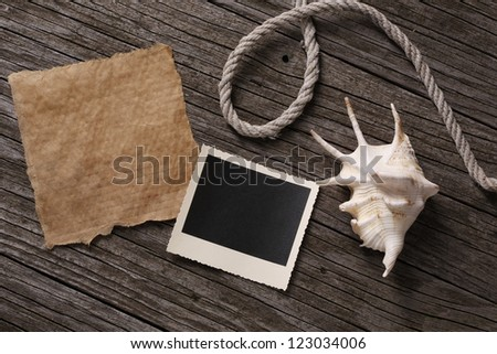 Blank paper and instant photo with shell and string  on wooden background - stock photo