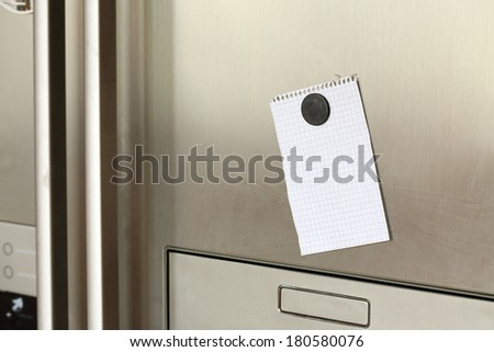 Blank paper and magnet on refrigerator door.