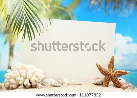 Blank paper card and seashells on sand beach. - stock photo