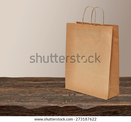 Blank paper craft shopping bag on wooden table with copyspace - stock photo