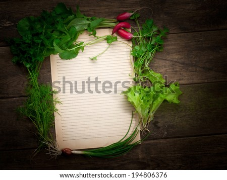 Blank paper for recipes with fresh herbs on old wooden table - stock photo