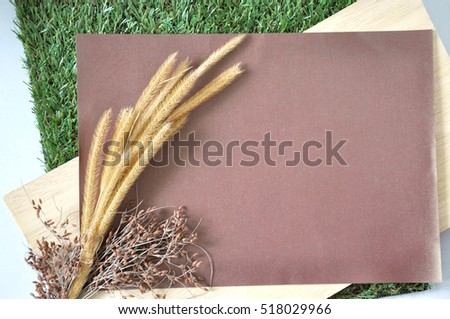 Blank paper for text decorate with dried flowers put on wooden and grass