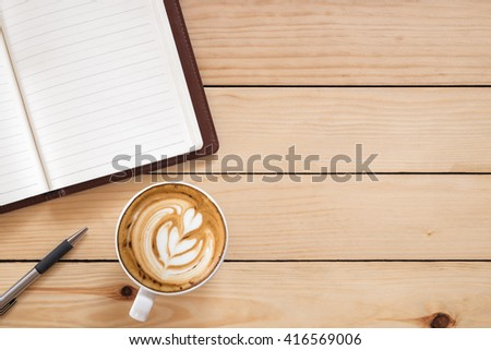 Blank paper leather notebook with pen and cup of coffee on wooden table.View from above.Office supplies and gadgets on desk table.Working desk table concept.Writing notes. - stock photo