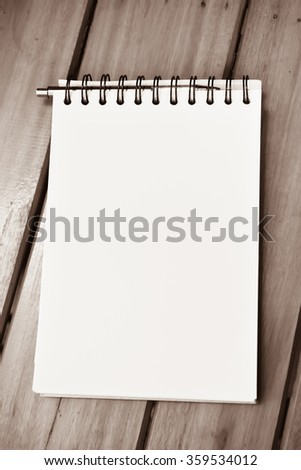 Blank paper note book on white wood - stock photo