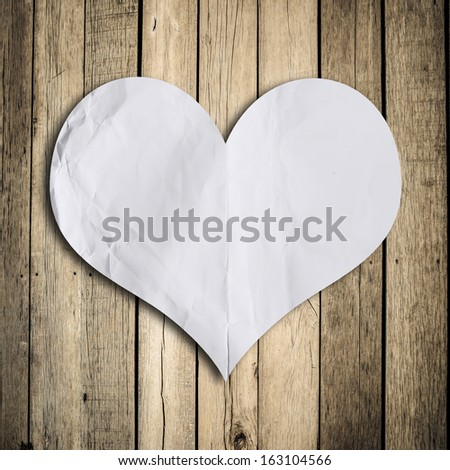 blank paper note with heart shape on grunge wooden background with copy space - stock photo