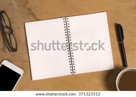 Blank paper note with office accessories and smartphone on vintage wooden table - stock photo