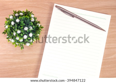 blank paper on desk / Open blank white paper notebook with copy space and a pen lying on a wood desk, view from above / for your text or message / top view - stock photo