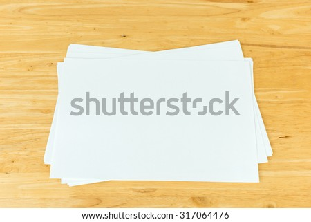 Blank paper on wood table  - stock photo