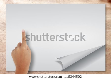 Blank paper page with hand point on wood background - stock photo