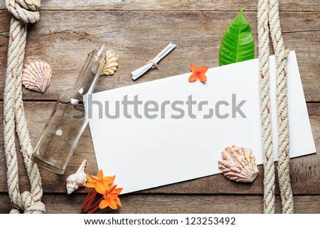 Blank paper sheet on weathered wood background with rope, shells, leaf and flowers - stock photo