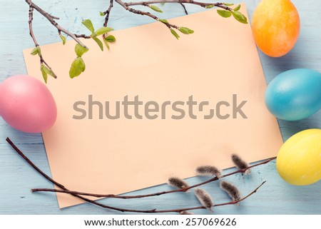 Blank paper sheet with easter eggs and pussy willow branches on blue painted wooden background - stock photo