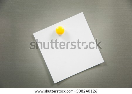 Blank paper sheet with yellow magnet on refrigerator door