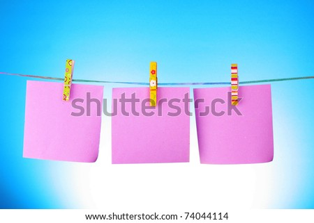 Blank paper sheets on a clothes line on a blue background