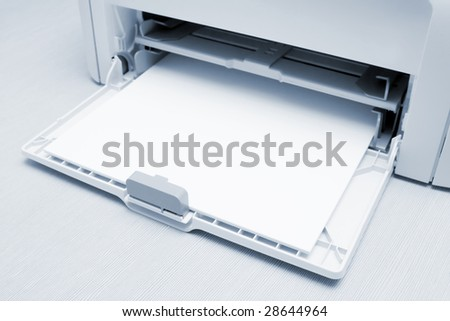 Blank paper-sheets ready for print in a printer. On the table in office. Toned in blue. - stock photo