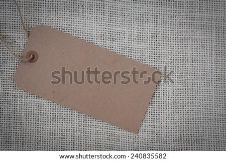 Blank Paper Tag on Burlap Background - stock photo