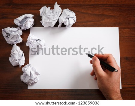 Blank paper waiting for idea with mans  hand and  pen - stock photo