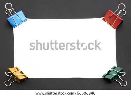 blank paper with colorful clip on black background