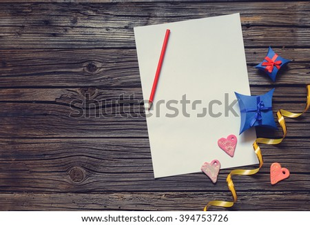 Blank paper with copy space on top of wooden surface beside Valentines Day hearts, ribbon, gift boxes and pencil - stock photo