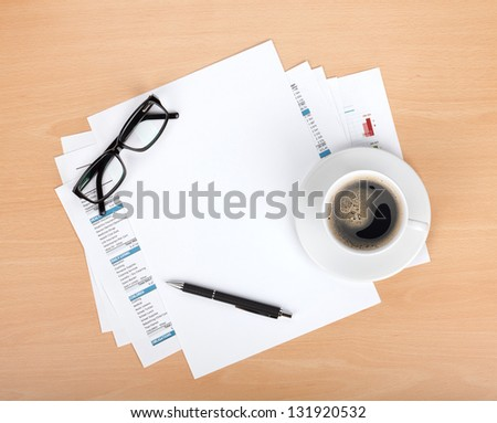 Blank paper with pen, glasses and coffee cup over financial documents - stock photo