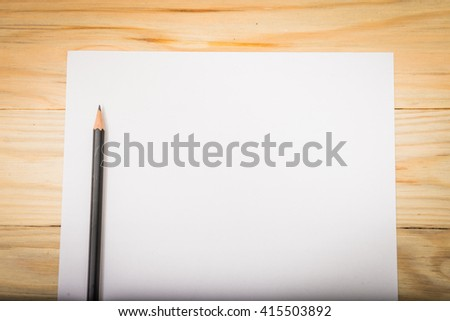 Blank paper with pencil on wood table
