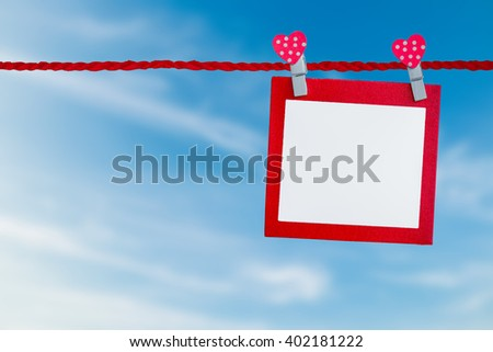Blank paper with rope on blue sky background.
