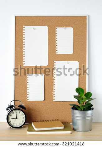 Blank papers on cork board, notebooks, alarm clock and tree on wood table over white cement wall background, template - stock photo