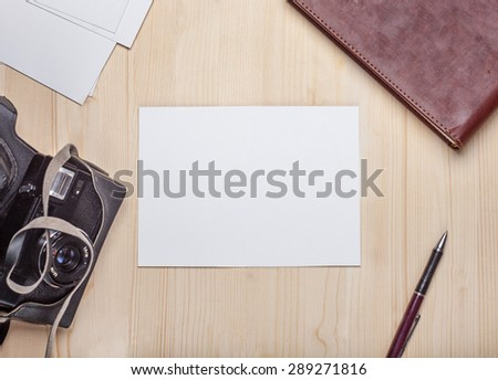 Blank photo card on a wooden table surrounded by camera, album, pen - stock photo