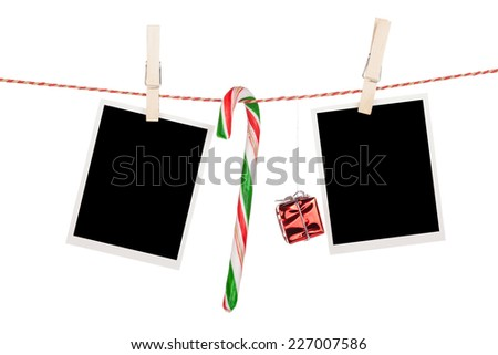 Blank photo frames and candy cane hanging on the clothesline. Isolated on white background - stock photo