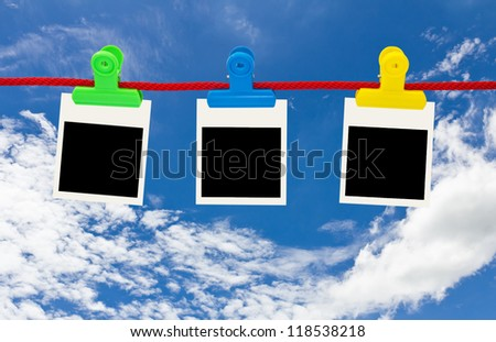 Blank photo frames Hanging by plastic peg on blue sky