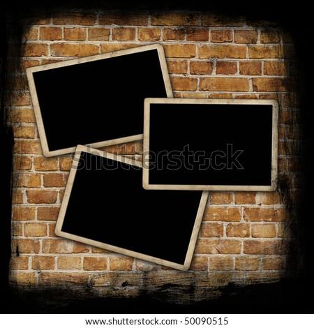 Blank photo frames on aged brick wall texture - stock photo