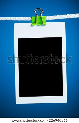blank photo hanging on rope, blue background - stock photo