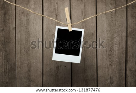 Blank photograph hanging clipped to the rope over wooden background with clipping path for the inside of the frame - stock photo