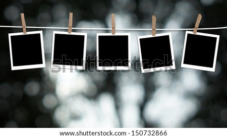 Blank photographs hanging on a clothesline against a Bokeh lights background - stock photo