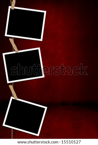 Blank photographs hanging on clothespins against a red grunge border - stock photo