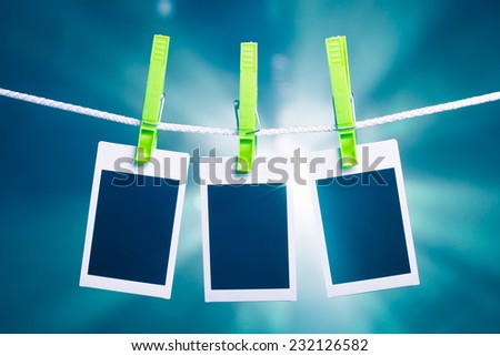 blank photos hanging on rope, blue lights background - stock photo
