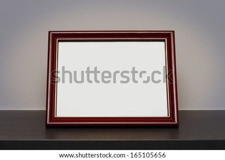 Blank picture frame at the desk - stock photo