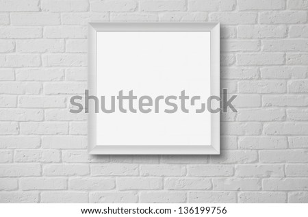 Blank picture frame at the white brick wall with copy space and clipping path - stock photo