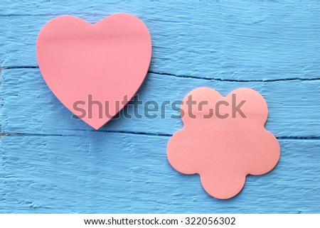 Blank pink paper note in two different shapes - flower and heart shape on grunge blue wooden background with copy space - stock photo