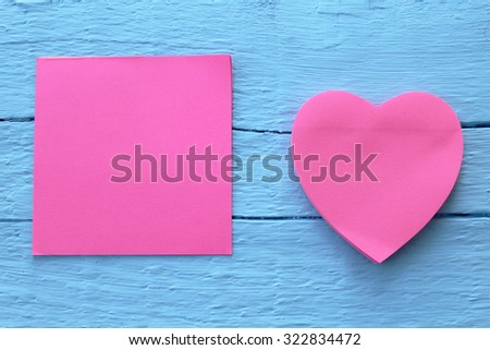 Blank pink paper note in two different shapes - square and heart shape on grunge blue wooden background with copy space - stock photo