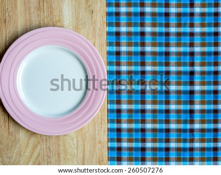 Blank pink plate on wooden table and checked tablecloth background - stock photo